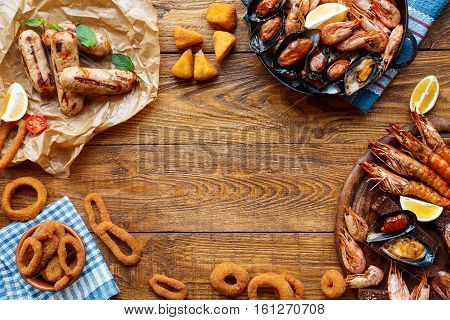 Seafood platter and meat on wood, frame background top view, flat lay. Mediterranean cuisine restaurant food, fried calamari rings, shrimps, mussels, oysters delicacy. Catering, banquet table mockup