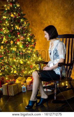 Young woman sits in a rocking-chair near Christmas-tree. She with a smile looks at beautifully decorated Christmas tree. Woman waits for guests. She has prepared many gifts.