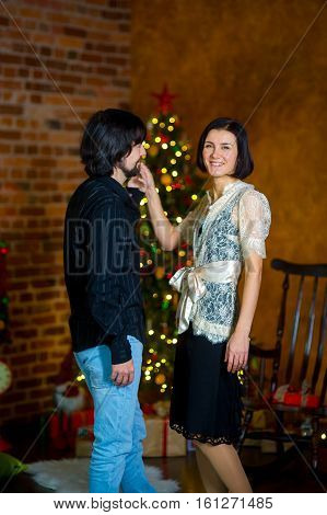Young nice man invites woman to dance. Elegantly dressed woman smiles. In a corner of the room the Christmas tree decorated with garlands shines. Under her there are a lot of gifts in beautiful boxes.