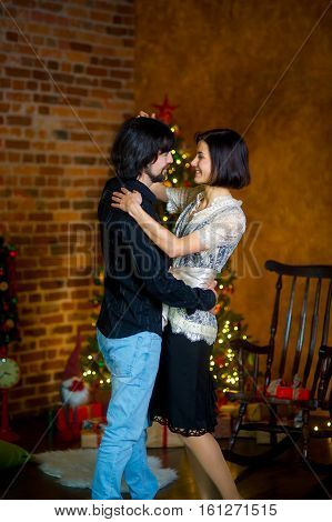 The beautiful young couple dances near the Christmas tree. Young people with love and tenderness look at each other. Under the Christmas tree there are a lot of gifts in beautiful boxes.