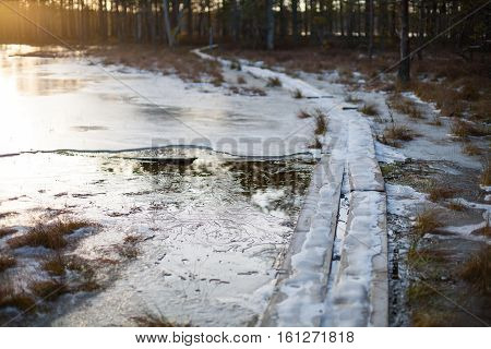 Cold winter sunset background of a bog landscape with a wooden boardwalk heading over a lake covered in ice