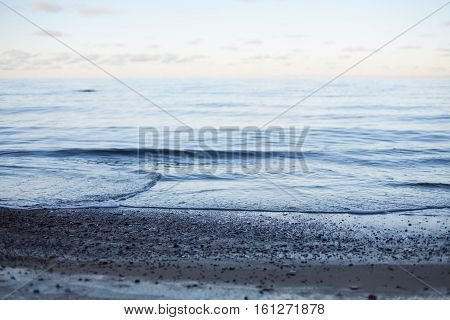 Abstract background of a pastel sunset on a peaceful sea with calm waves wafting to the shore