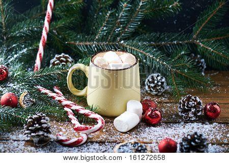 mug with hot chocolate, christmas tree, tangerines, peppermint stick and marshmallow on a snow wooden background. Dark photo. Empty space for text.