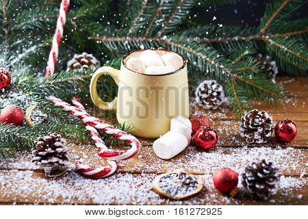 mug with hot chocolate, christmas tree, tangerines, peppermint stick and marshmallow on a snow wooden background with falling snow. Dark photo.