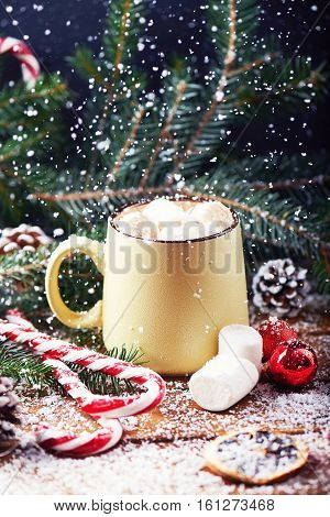 mug with hot chocolate, christmas tree, tangerines, peppermint stick and marshmallow on a snow wooden background with falling snow. Dark photo. Toned for art effect. Vertical shot
