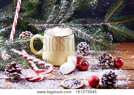 mug with hot chocolate, christmas tree, tangerines, peppermint stick and marshmallow on a snow wooden background with falling snow. Dark photo. Empty space for text. Toned for art effect.