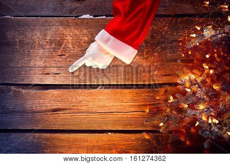 Christmas Santa Claus showing empty copy space by hand for text. Pointing finger, Proposing product. Advertisement gesture presenting point. Point to gift, text or product over wooden background.