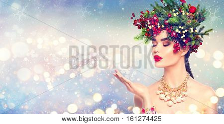 Christmas Winter Fashion Girl blowing with Magic snow in Her Hand. Fairy. Beautiful New Year and Xmas Tree Holiday Hairstyle, Makeup. Gift. Beauty Model woman on Holiday Blurred blue Background, sales