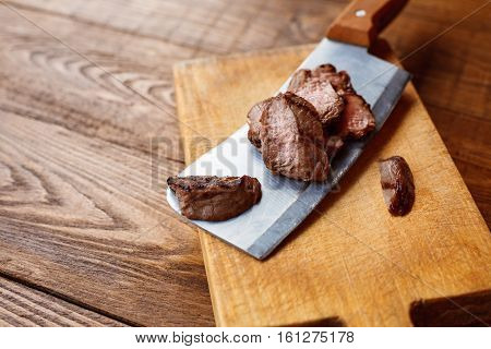Cleaver butcher's knife slicing grilled steak on meat cutting board on wooden background. Fresh juicy roasted meat cuts. Chef cooking
