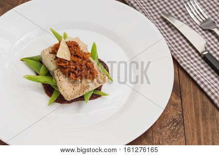 Cooked fish with steamed asparagus, vegetable ragout, tomato sauce and potato chips