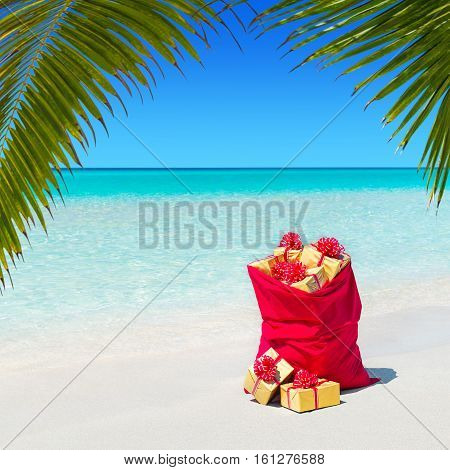 Red Christmas sack full of wrapped gift boxes at tropical ocean palm beach. Travel agency price reduction for Happy New Year hot tours destinations concept.