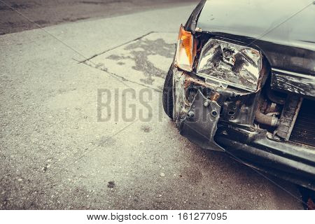 Color image of a crashed car with broken headlight.