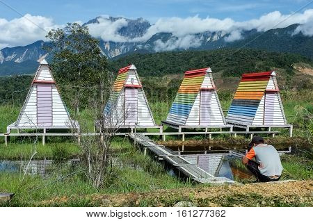 Ranau,Sabah-Dec 11,2016:Photographer taking picture of colorful huts at the Mt Kinabalu Holiday Camp at Ranau,Sabah,Borneo with background of the Mountain Kinabalu during sunny day on 11th Dec 2016.