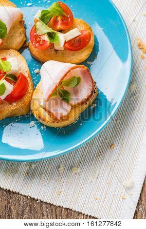 Traditional Italian antipasti bruschetta with tomato, cheese and bacon.
