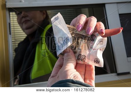 The Denomination Of 50 Rubles In His Hand Stretched Out To Pay For Travel On Toll Road