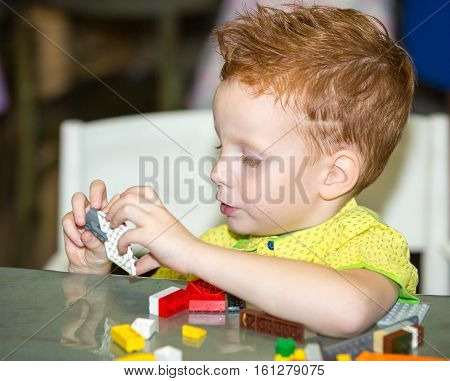 Boy child playing with the constructor  in preschool at the table in kindergarten
