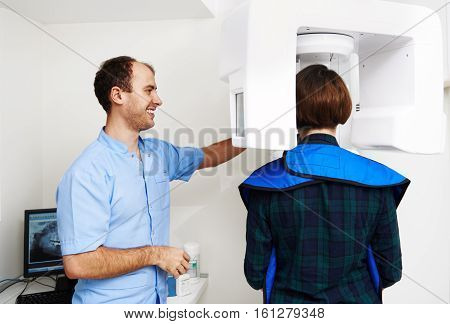 Medical equipment. Dental technology. Portrait of smiling male practitioner taking digital teeth x-ray in radiography cabinet.