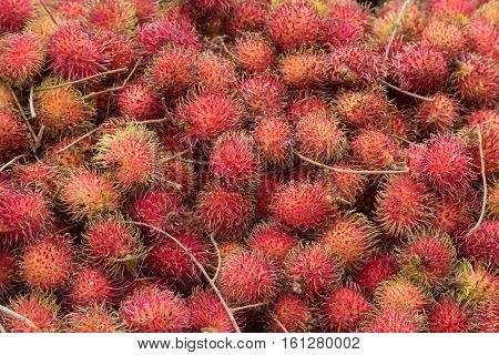 Ripe juicy exotic fruit rambutans at tropical marketplace