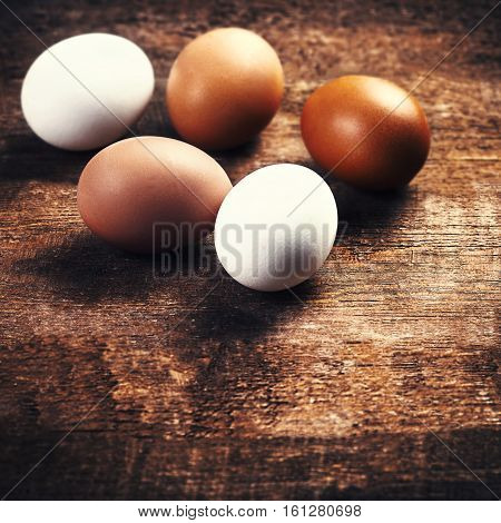 Farm eggs on a wooden rustic background. Fresh brown and white eggs close up with copy space