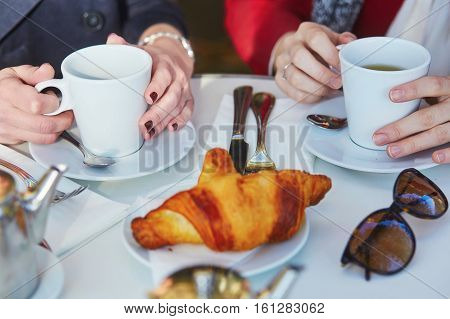 Two girls in Parisian outdoor cafe drinking coffee with croissant. Closeup of female hands with coffee cups. Friendship concept
