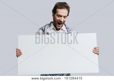 Wow! Young confident man in smart casual clothes holding blank flipchart with surprised face while standing against grey background
