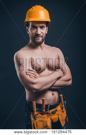 Muscular construction worker. Young confident man keeping arms crossed and looking at camera while standing against black background