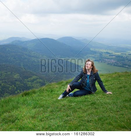 Girl Sitting On The Slope Of Volcano In Auvergne
