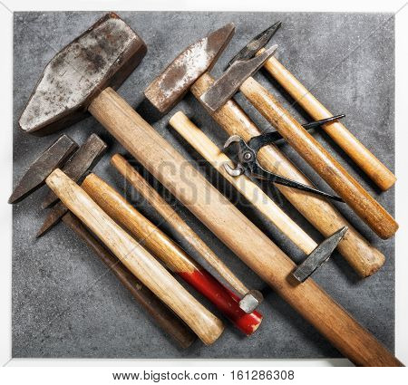 Tool background. Old vintage hammer and pincers collection on grunge stone workbench. Top view flat lay