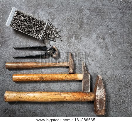 Tool background. Old vintage hammer nails and pincers collection on grunge stone workbench. Copy space. Top view flat lay
