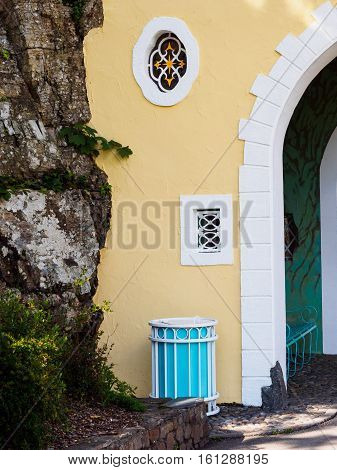 Colourful waste bin near on of the two gateway arches leading into Portmeirion Village Gwynedd Wales.