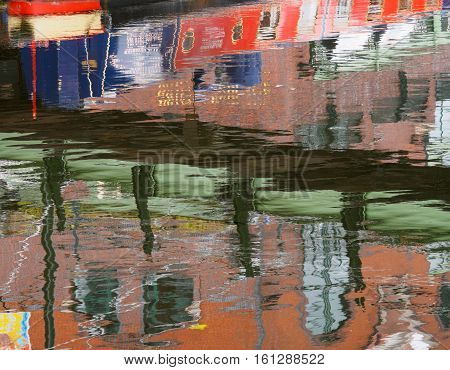 Reflections of colourful narrow boats and buildings in the canalat Gas Street Basin in Birmingham.