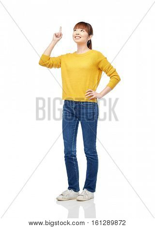 people, ethnicity and idea concept - happy asian young woman pointing finger up over white