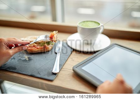 food, dinner, technology and people concept - woman with tablet pc computer and matcha green tea latte eating salmon panini sandwich at restaurant