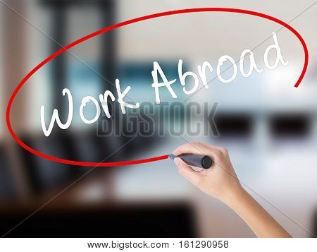 Woman Hand Writing Work Abroad With A Marker Over Transparent Board