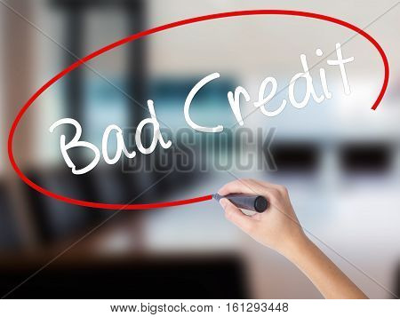 Woman Hand Writing Bad Credit With A Marker Over Transparent Board