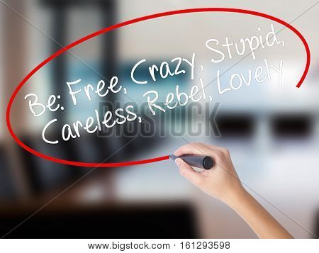 Woman Hand Writing Be: Free, Crazy, Stupid, Careless, Rebel, Lovely With A Marker Over Transparent B