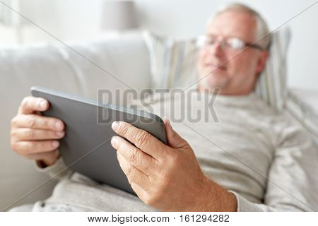 technology, old age, people and lifestyle concept - happy smiling senior man with tablet pc computer lying on sofa at home