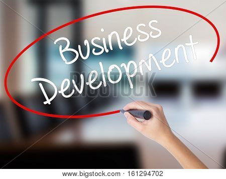 Woman Hand Writing Business Development With A Marker Over Transparent Board.