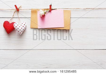 Valentine background with red paper hearts row border on clothespins and paper card with rose flower on rustic wood planks. Happy lovers day mockup, copy space