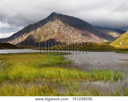 is a mountain in the Ogwen Valley,Snowdonia, Wales. It forms part of theGlyderaugroup, and is one of the most famous and recognisable peaks in Britain, having a classic pointed shape with ruggedcrags. At 917.5m (3,010ft) above sea level it is the fi