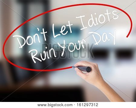 Woman Hand Writing Don't Let Idiots Ruin Your Day With A Marker Over Transparent Board