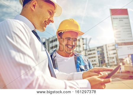 business, building, teamwork, technology and people concept - smiling builders in hardhats with tablet pc computer at construction