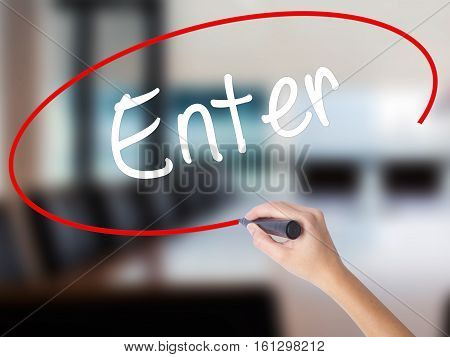 Woman Hand Writing Enter With A Marker Over Transparent Board