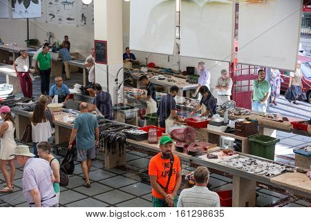 FUNCHAL, MADEIRA, PORTUGAL - SEPTEMBER 2, 2016: Fish sellers at Mercado dos Lavradores the famous fish and seafood market of Funchal the capital of Madeira island