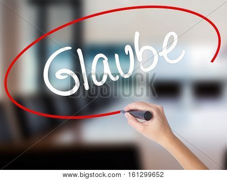 Woman Hand Writing Glaube (believe In German) With A Marker Over Transparent Board.