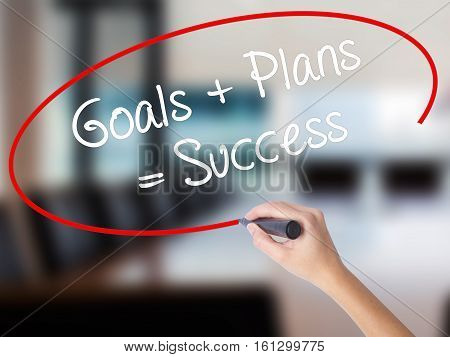 Woman Hand Writing Goals + Plans = Success With A Marker Over Transparent Board.