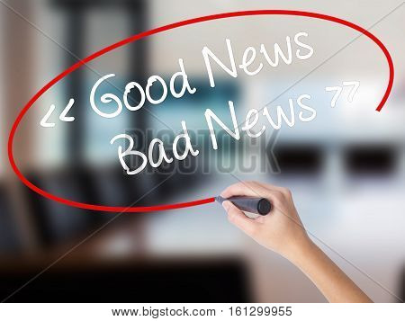 Woman Hand Writing Good News - Bad News With A Marker Over Transparent Board.