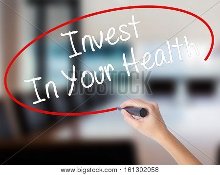 Woman Hand Writing Invest In Your Health With A Marker Over Transparent Board.