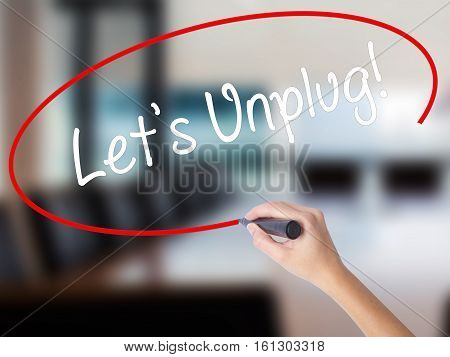 Woman Hand Writing Let's Unplug! With A Marker Over Transparent Board
