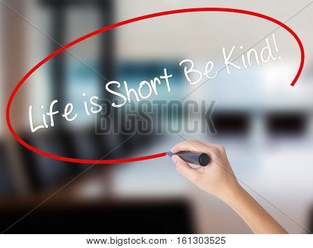 Woman Hand Writing Life Is Short Be Kind! With A Marker Over Transparent Board